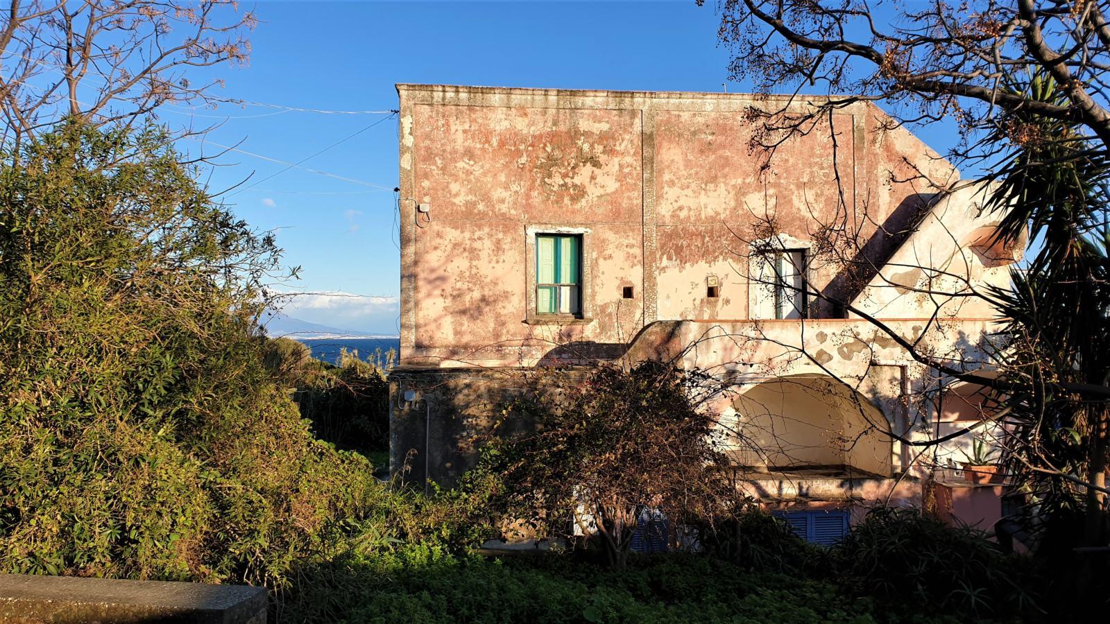 Una casa dai muri in calce rosa e dalle persiane azzurre a picco sul mare di Procida