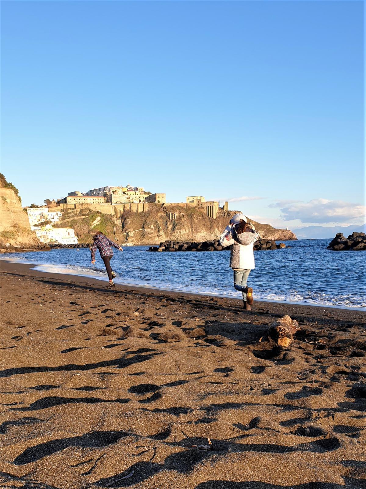 Due bambine che si rincorrono sulla spiaggia nera di Chiaia sull'isola di Procida
