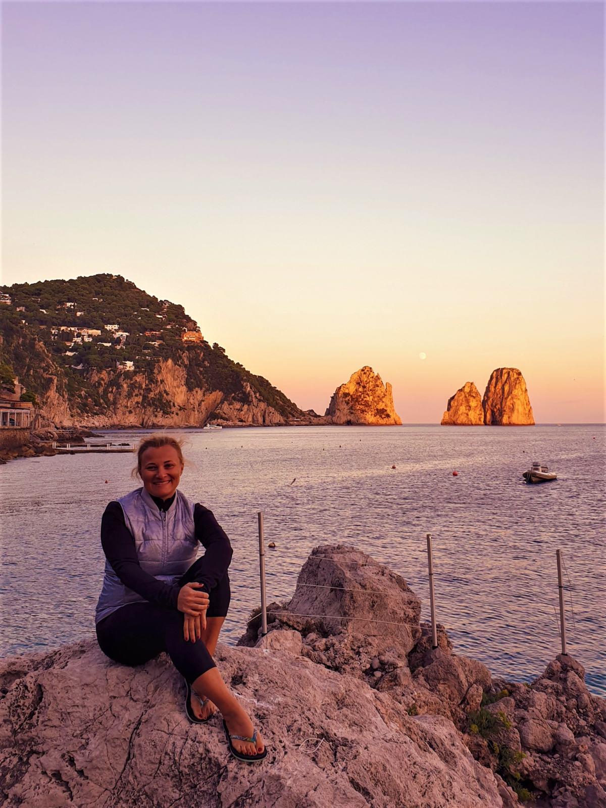 Io seduta in spiaggia e alle mie spalle i Faraglioni di Capri all'ora del tramonto