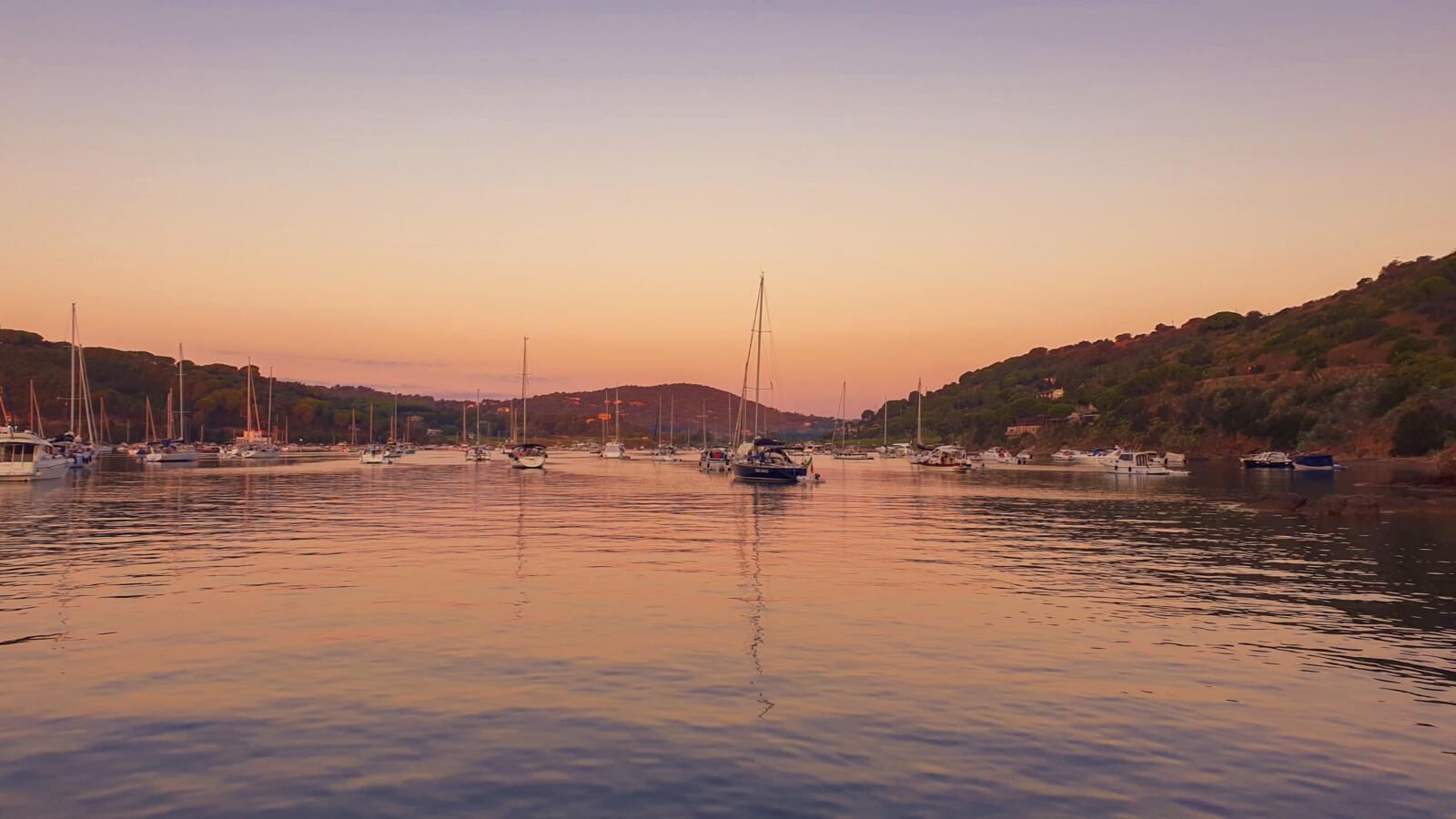 Alba in barca a vela vista dalla baia di Porto Azzurro