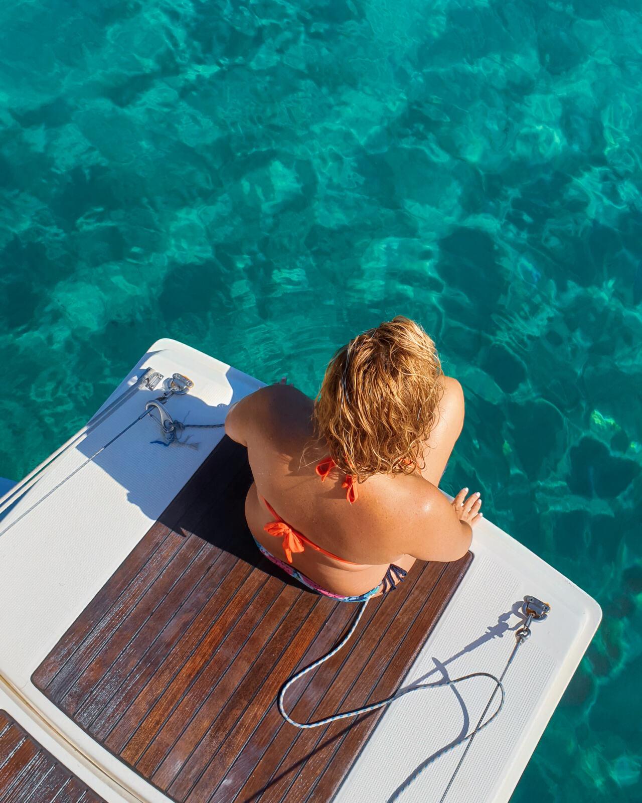 Io seduta a poppa di una barca a vela